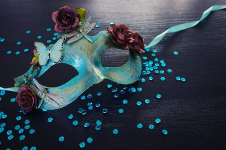 Photo of elegant and delicate blue Venetian mask over dark wooden background