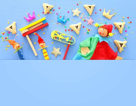 Purim celebration concept (jewish carnival holiday) over blue wooden background. Top view, Flat lay
