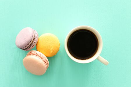 White cup of coffee and colorful macaron or macaroon over pastel wooden table