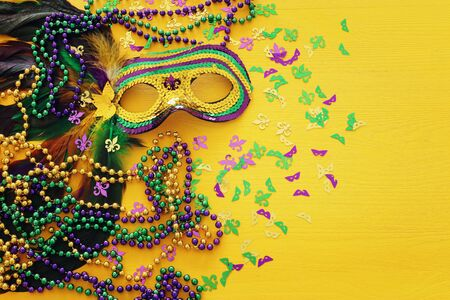 Holidays image of mardi gras masquarade venetian mask over yellow background. view from above