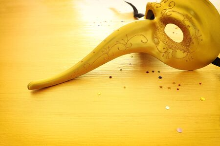 Venetian mask with a long nose over gold background