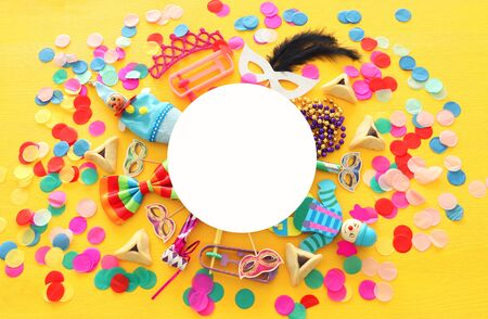 Purim celebration concept (jewish carnival holiday) over yellow wooden background. Top view, Flat lay Stock Photo