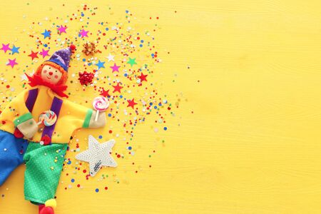 Party colorful noisemaker and cute clown over yellow wooden background . Top view, flat lay