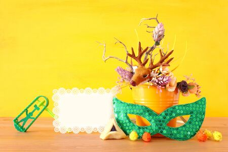 Purim celebration image (jewish carnival holiday) with traditional hamantasch cookies and deer antlers floral decoration over yellow wooden background