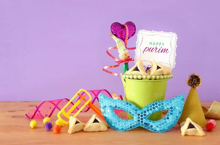 Purim celebration concept (jewish carnival holiday) over purple wooden background