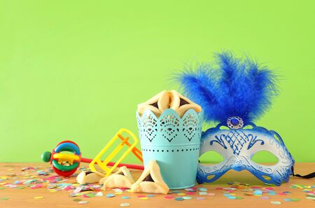 Purim celebration concept (jewish carnival holiday) over green wooden background