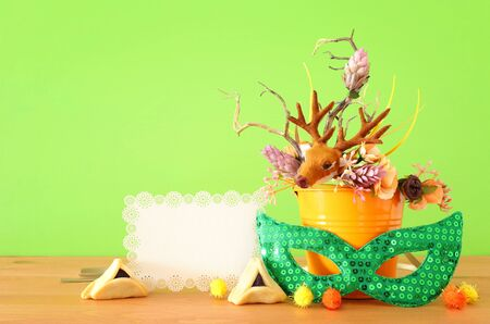 Purim celebration image (jewish carnival holiday) with traditional hamantasch cookies and deer antlers floral decoration over green wooden background