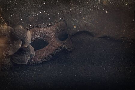 Photo of elegant and delicate black Venetian mask over dark glitter background