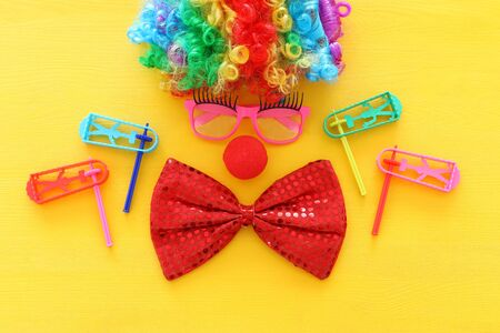 carnival, party and Purim celebration concept (jewish carnival holiday) with clown wig, glasses and red nose over yellow background