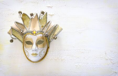 elegant traditional venetian mask over distressed old white wooden background