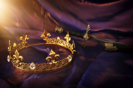 low key image of beautiful queen/king crown and sword over dark royal purple delicate silk. fantasy medieval period Foto de archivo