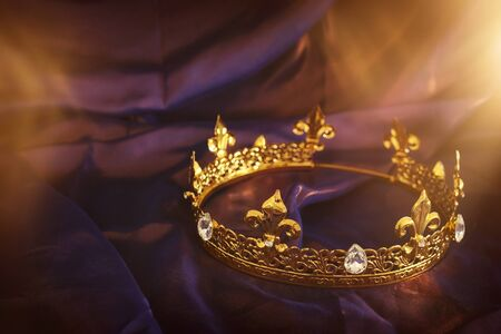 low key image of beautiful queenking crown over dark royal purple delicate silk. fantasy medieval period