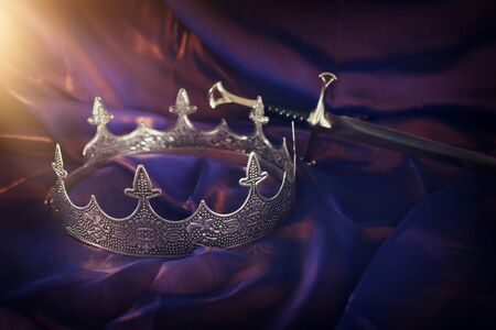 low key image of beautiful queenking crown and sword over dark royal purple delicate silk. fantasy medieval period