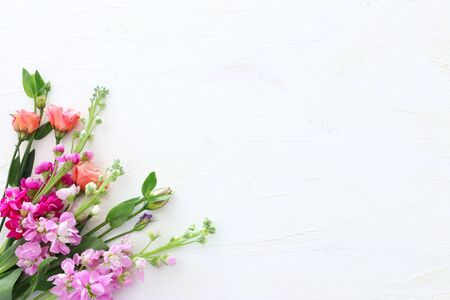 spring bouquet of pink flowers over white vintage wooden background. top view, flat lay