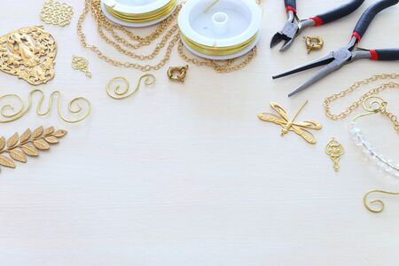 Jewellery making concept with gold chain, filigree charms and tools over white wooden background