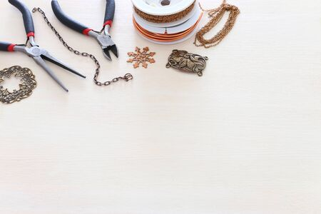 Jewellery making concept with brass chain, filigree charms and tools over white wooden background
