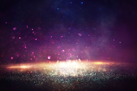 background of abstract glitter lights. gold, black and purple. de focused