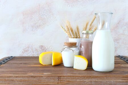 photo of dairy products over old wooden table and white background. Symbols of jewish holiday - Shavuot Фото со стока