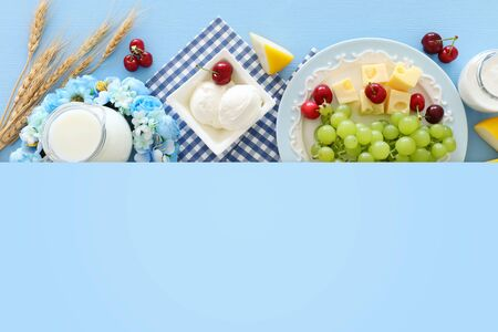 Top view photo of dairy products over pastel blue background. Symbols of jewish holiday - Shavuot