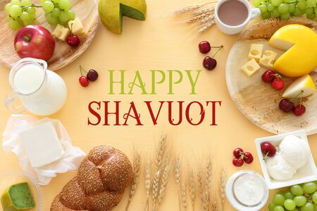 Top view photo of dairy products over pastel yellow background. Symbols of jewish holiday - Shavuot
