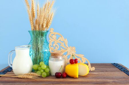 photo of dairy products over old wooden table and pastel background. Symbols of jewish holiday - Shavuot