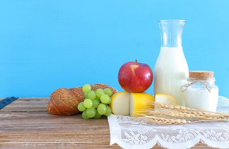 photo of dairy products over old wooden table and blue background. Symbols of jewish holiday - Shavuot