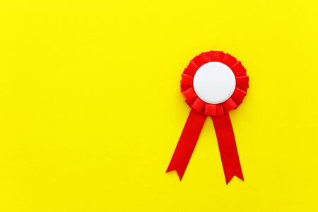 Red award rosette with ribbons over yellow textured background, ready for mock up