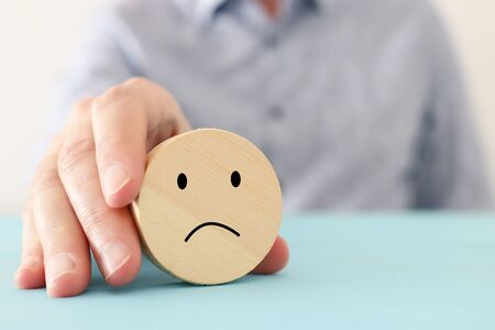 male hand holding wooden cube with sad face. concept of anxiety, stress or sad emotions 免版税图像