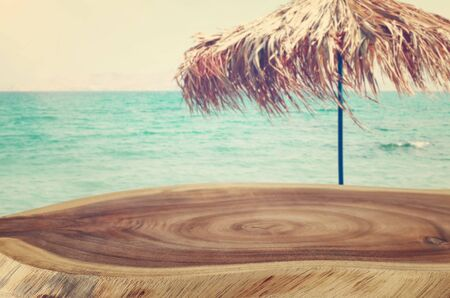 background Image of wooden table in front of tropical beach. Ready for product display