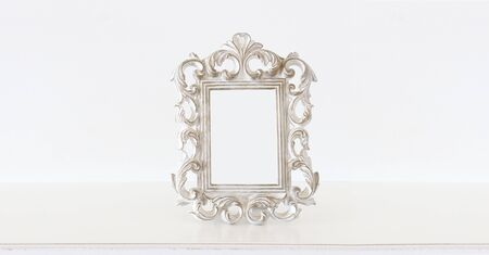 Image of white baroque vintage empty photo frame over wooden table. For mockup, can be used for photography montage Archivio Fotografico