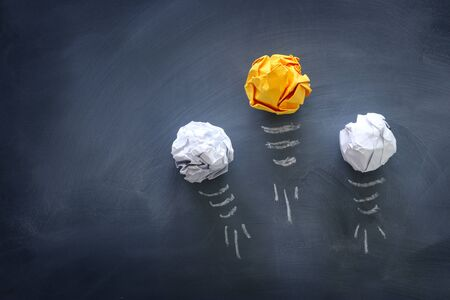 Education concept image. Creative idea and innovation. Crumpled paper as light bulb metaphor over blackboard Imagens