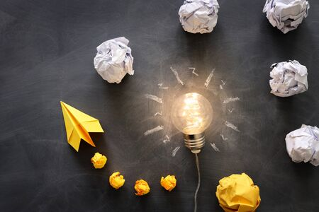 Education concept image. Creative idea and innovation. Light bulb as metaphor over blackboard