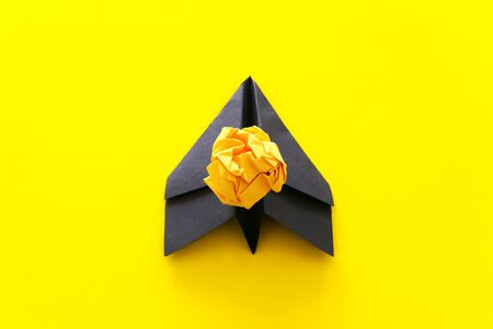 education or innovation concept. balck paper origami plane over yellow background