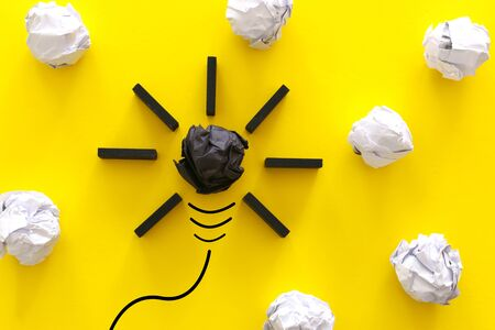 Education concept image. Creative idea and innovation. Crumpled paper as light bulb metaphor over yellow background Imagens