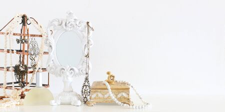 Image of white vintage mirror and pearls over wooden table. For mockup, can be used for photography montage