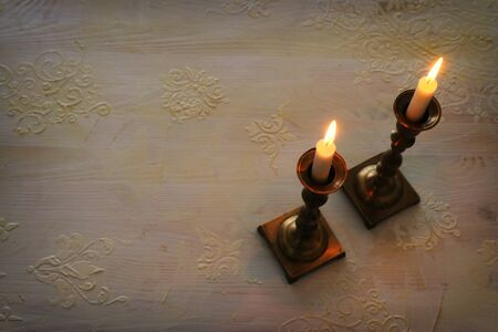 two shabbat candlesticks with burning candles over wooden table. top view. low key Archivio Fotografico