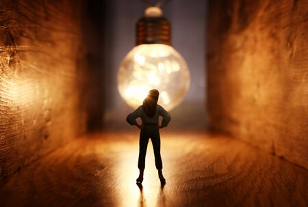 Surreal image of person in dark corridor looking at glowing light bulb. Concept of finding the right idea, or way out Foto de archivo - 150379758