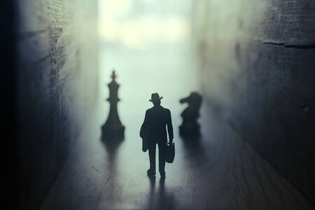 Businessman walks on an unknown road and chess at the end