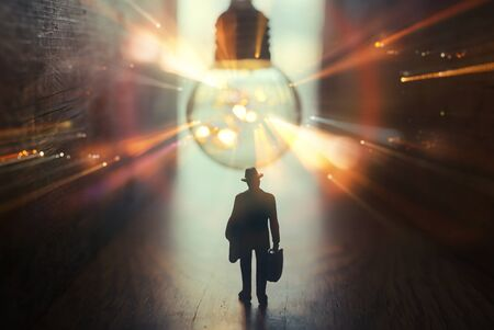 Surreal image of person in dark corridor looking at glowing light bulb. Concept of finding the right idea, or way out