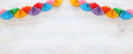 Paper colorful chain garland over white wooden background. Traditional jewish sukkot holiday decoration Archivio Fotografico