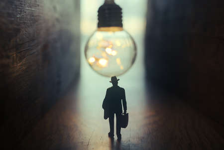 Surreal image of person in dark corridor looking at glowing light bulb. Concept of finding the right idea, or way out Archivio Fotografico - 151071413