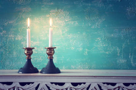 two shabbat candlesticks with burning candles over wooden table