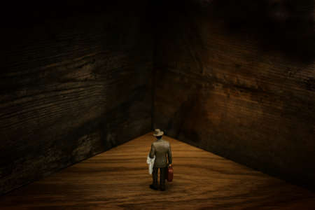 A concept image of a man who facing a dead end and has a wall in front of him. An idea of overcoming fear and obstacles