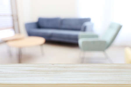 Wooden empty table in front of Living room sofa interior. For product display and presentation