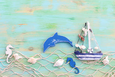 wooden vintage boat, dolphin, fishnet and sea shells over blue background