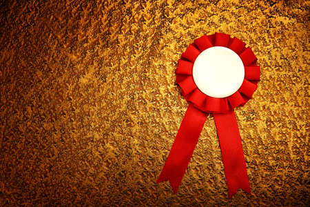 Red award rosette with ribbons over luxury gold brass textured background, ready for mock up
