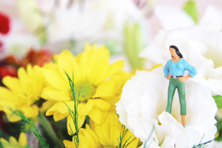 Concept image of a woman figurine and flowers. An idea of social expectations, gender and metaphorical perception of the female figure
