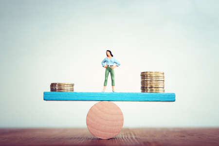 Concept image of woman balancing stack of coins on seesaw