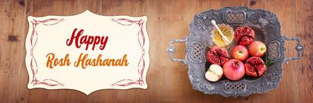 rosh hashanah (jewesh holiday) concept - honey, pomegranate and apple traditional symbols