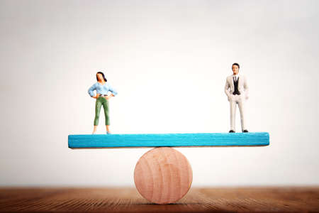 Concept image of gender equality. man and woman balancing on seesaw